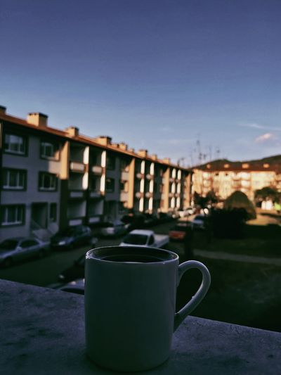 Close-up of coffee cup on table against buildings in city