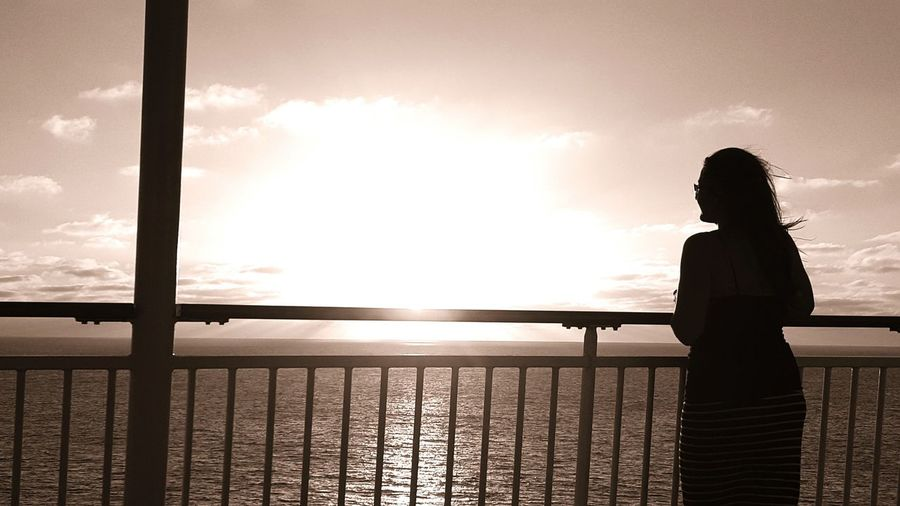 Silhouette woman standing by railing while looking at sea against sky