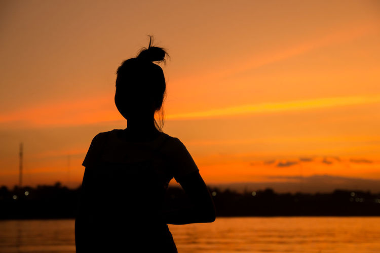 Silhouette young woman standing by sea against orange sky during sunset