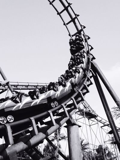 Low Angle View Of People In Rollercoaster Against Sky