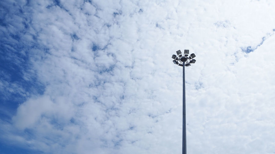 Low angle view of light bulbs hanging against sky
