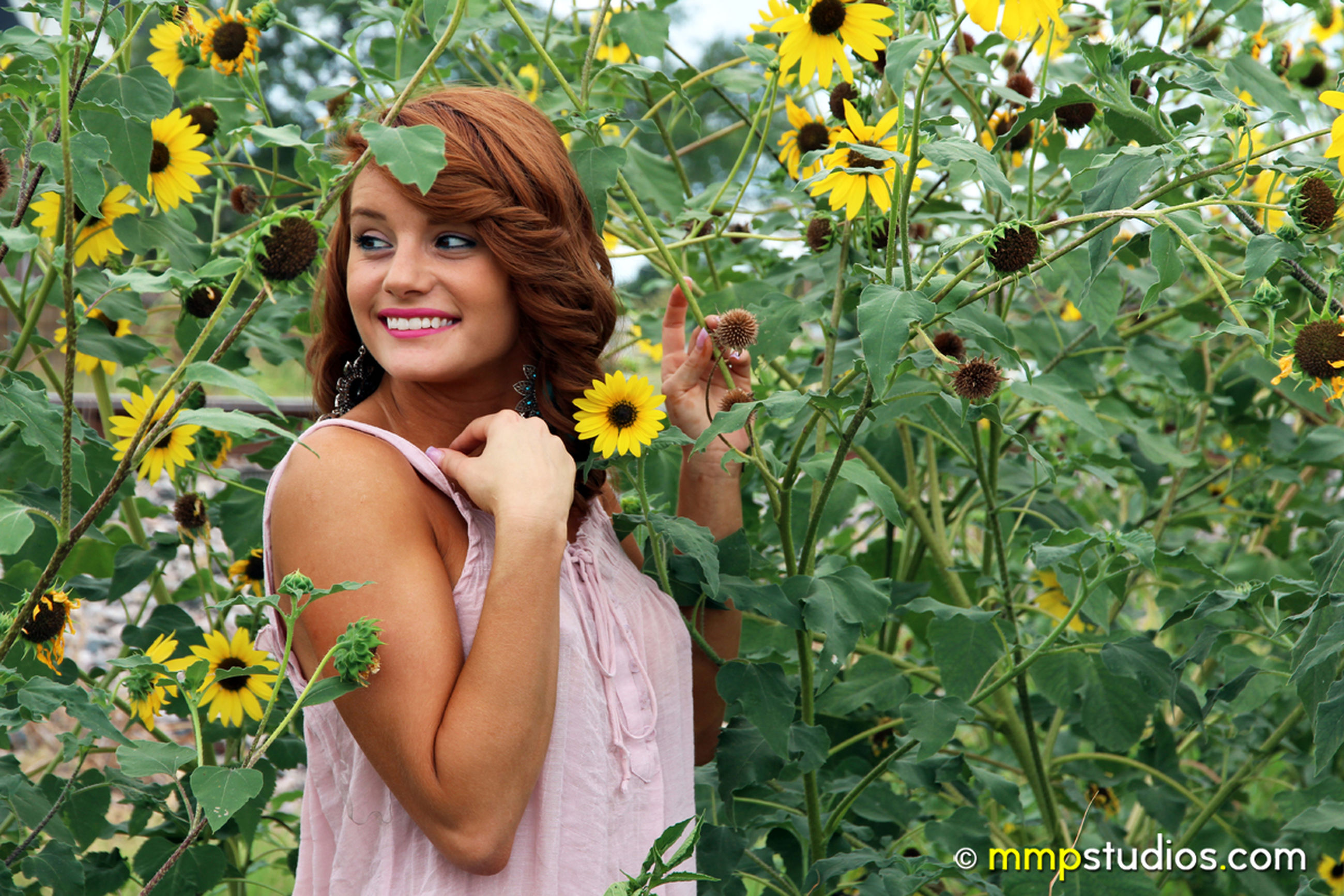plant, one person, looking at camera, smiling, portrait, growth, young adult, real people, young women, leaf, plant part, leisure activity, flowering plant, lifestyles, flower, women, nature, happiness, standing, day, beautiful woman, flower head, hairstyle, outdoors, sunflower