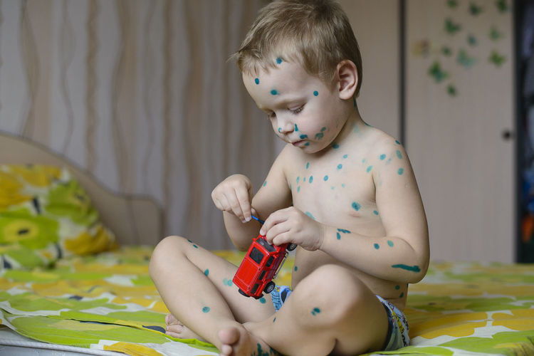 Child Childhood Young Baby One Person Real People Sitting Toy Babyhood Innocence Multi Colored Day Shirtless Toddler  Indoors  Holding Front View Hands People Bedroom Playing Green Color Virus Doctor