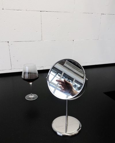 Close-up of wine glass by mirror on table against wall