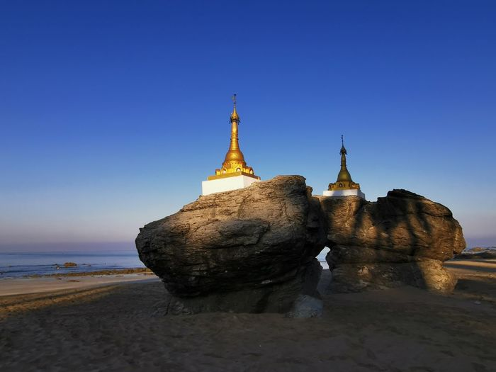 View of temple on beach against clear sky