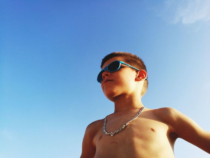Low Angle View Of Shirtless Boy Wearing Sunglasses Against Clear Sky