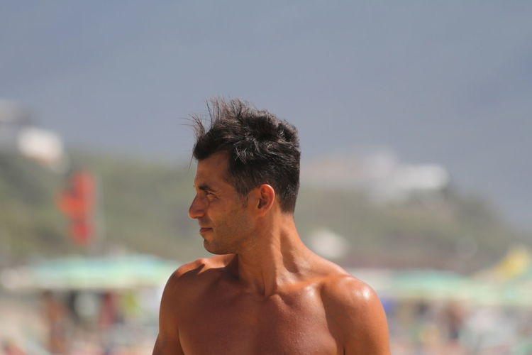 Close-up of shirtless young man standing at beach against sky