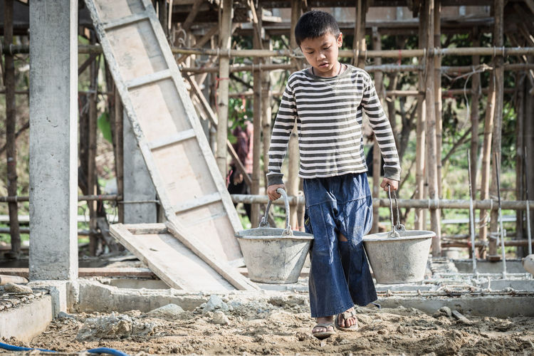 The concept of illegal child labor, children are forced to work construction. children violence.