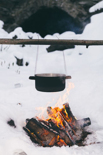 Food in a cauldron on a fire. Cooking outdoors in cast-iron cauldron. Burning Camping Day Flame Heat - Temperature Nature No People Outdoors Snow Winter
