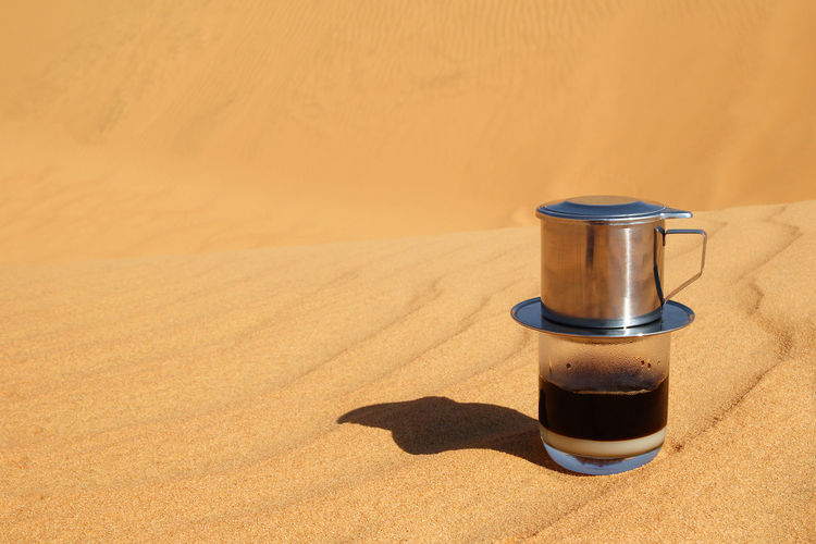 Drip Black Coffee in Vietnamese style with condensed milk on a red sand with copy method of making in a desert. Breakfast Coffee Condensed Milk Copy Space Desert EyeEmNewHere Lifestyle Loneliness Morning Nature Sunlight Aroma Brewing Coffee Energy Hot Drink Making Coffee Minimalism Morning Rituals No People Sand Sand Dune Shadow Still Life Traditional Vietnamese Coffee