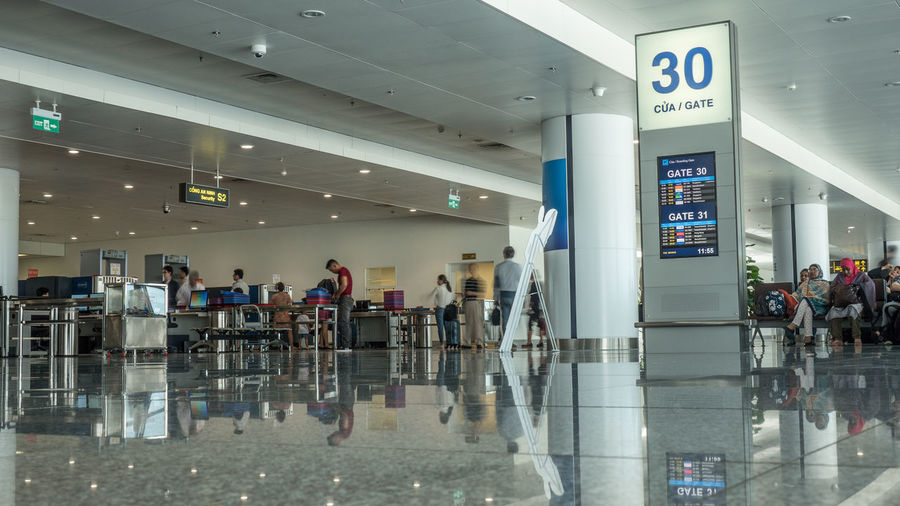 HANOI, VIETNAM - OCTOBER 27, 2015: Low angle shot of airport hall with gate information and people in security checkpoint. Noi Bai International Airport, the biggest one in northern Vietnam Airport ASIA Check Checkpoint Control Departure Gate Hall Hanoi Horizontal Illuminated Indoors  Lounge Nội Bài People Security Terminal Traveler Vietnam Wait
