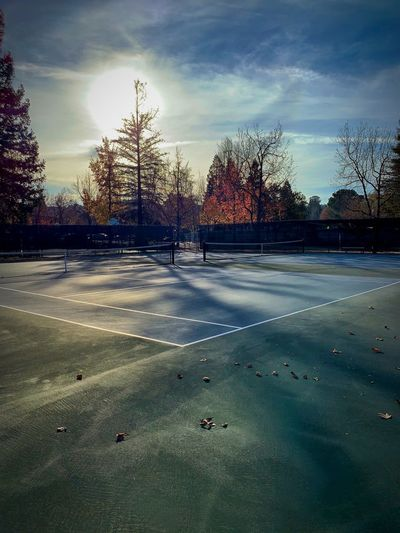 """No Game"" Tennis courts in a local city park in The San Francisco East Bay Area, sit idle with only shadows and autumn trees as their companion. Sun Shadows Empty Tennis 🎾 Tennis Court Tenniscourt Fall City Park City Parks California Autumn City Streets  Sky Cloud - Sky No People Sunlight"
