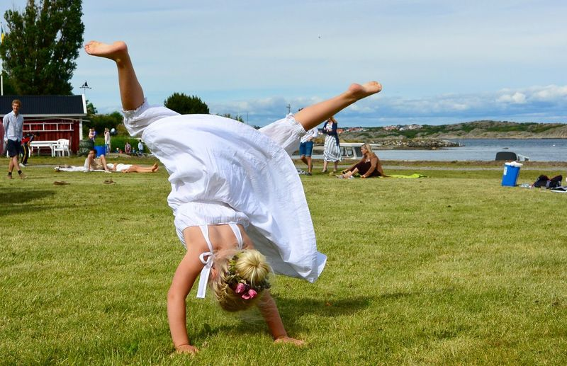 Rear view of girl practicing cartwheel at park