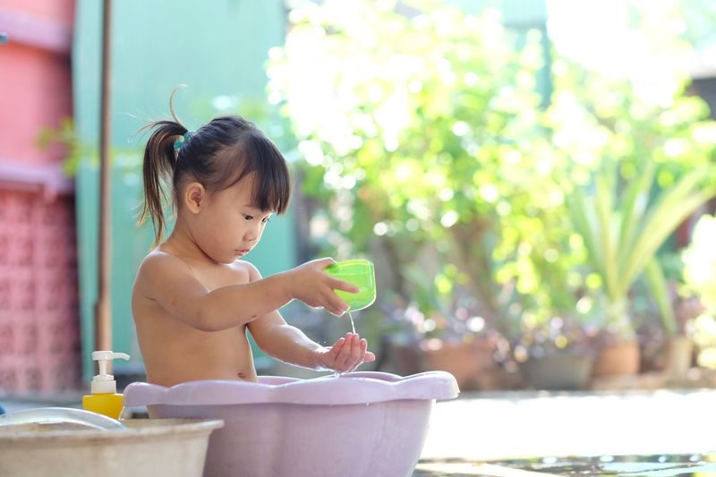 Little girl playing water in the plastic basin happily in the garden. Cute Kids Child Girl Basin Bathtub Bath Water Playing Tub Child Young Baby Childhood One Person Sitting Innocence Water Focus On Foreground Cute Babyhood Nature Real People Shirtless Outdoors Day Refreshment