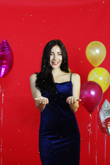 Portrait of a smiling young woman with red balloons