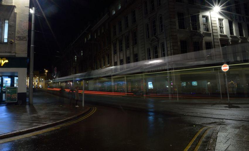 Train on illuminated road in city at night