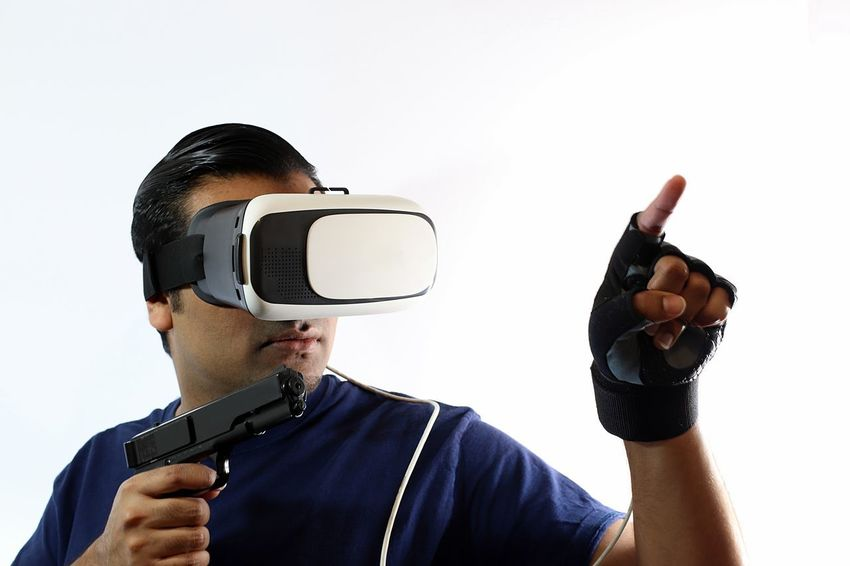Young man with virtual reality headset holding gun wearing gloves and pointing with gun in hand Console Display Futuristic Gamer Gaming Glasses Gloves Goggles Gun Headset Innovation New Pistol Playing Riffle Role Playing Game Shooter Shooting Technology Virtual Virtual Reality War Weapon White Background Wireless Technology