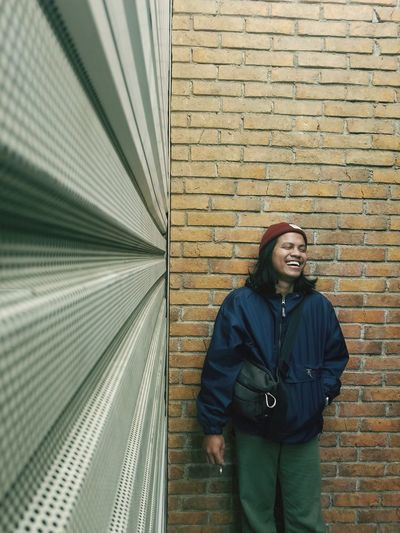 Portrait of smiling man standing against brick wall