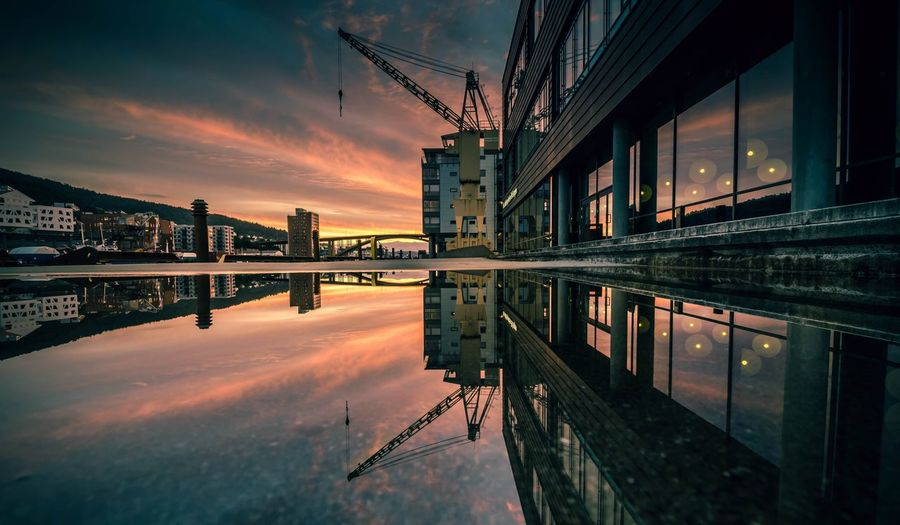 Crane And Buildings Reflecting On Puddle Against Orange Sky