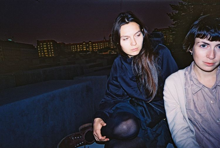 Female friends sitting on building terrace against sky at night