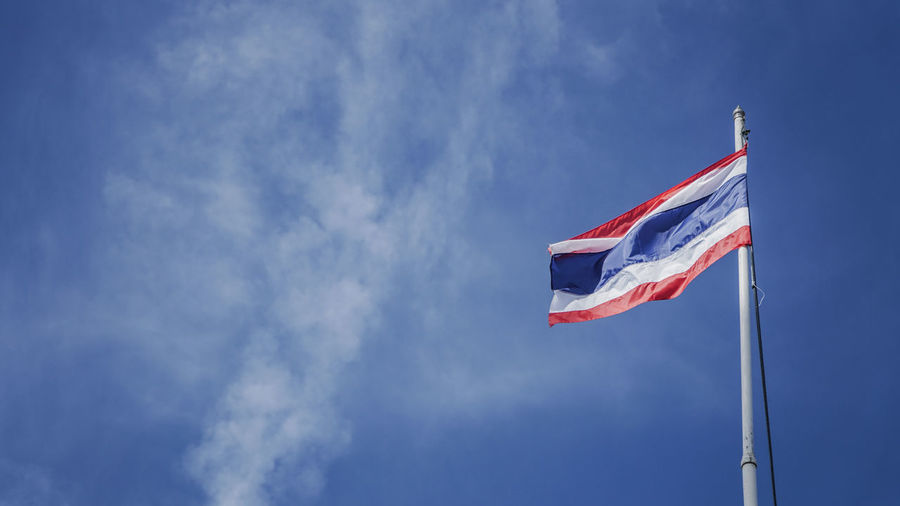 Low angle view of thai flag waving against blue sky