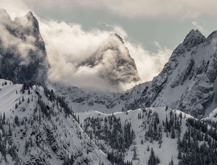 Clouds covering snowcapped mountains