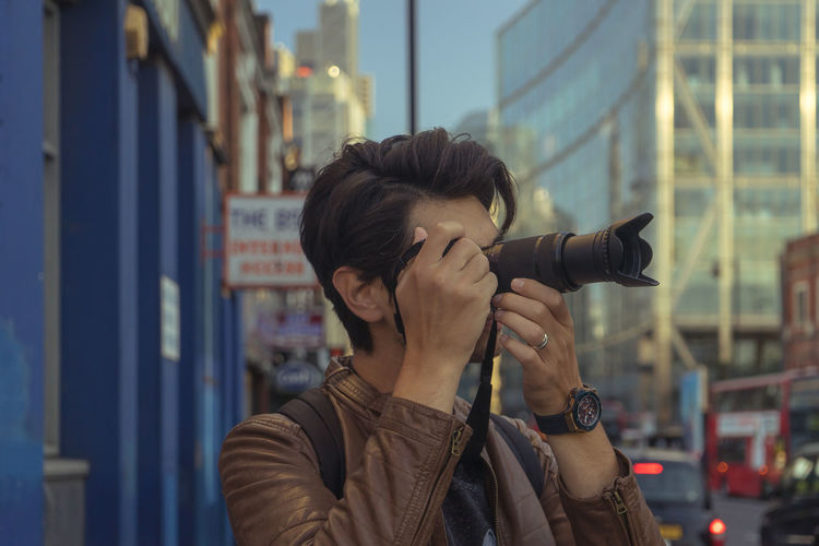 Close-Up Of Man Photographing While Standing In City
