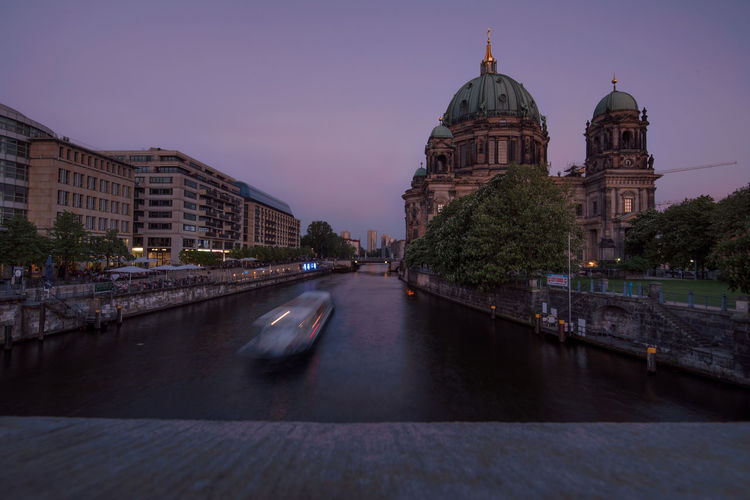 Blurred motion of ferry sailing over spree river by berlin cathedral