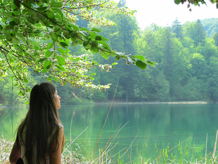 Rear view of woman standing by lake against trees
