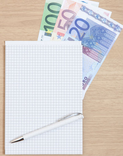 High Angle View Of Pen And Note Pad With Various Euro Notes On Table