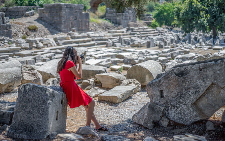 Girl in Red Dress and Slippers Taking Photos in Shadow of Trees in front of Ruins in Sunlight. Attractions Butterfly Camera Dress Ephesus Ruins Fashion Girl Lady Landmarks Leaning Tower Light Photographing Relaxing Rocks And Water Ruins Selçuklu Shade Shadows SLICE Summertime Taking Photos Tourists Travel Turkeyphotooftheday Visiting Woman
