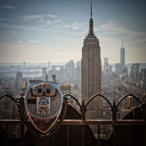 Coin-operated binoculars by empire state building in city against sky during sunset