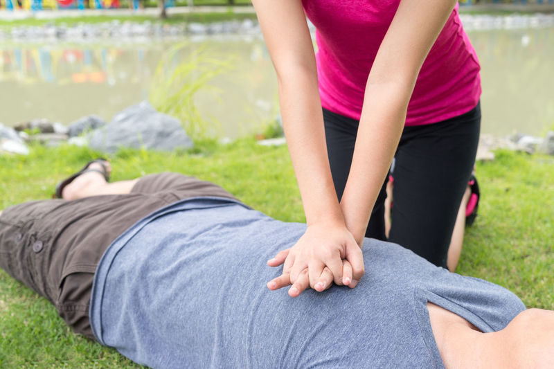 Midsection of woman giving cpr to man by lake on field