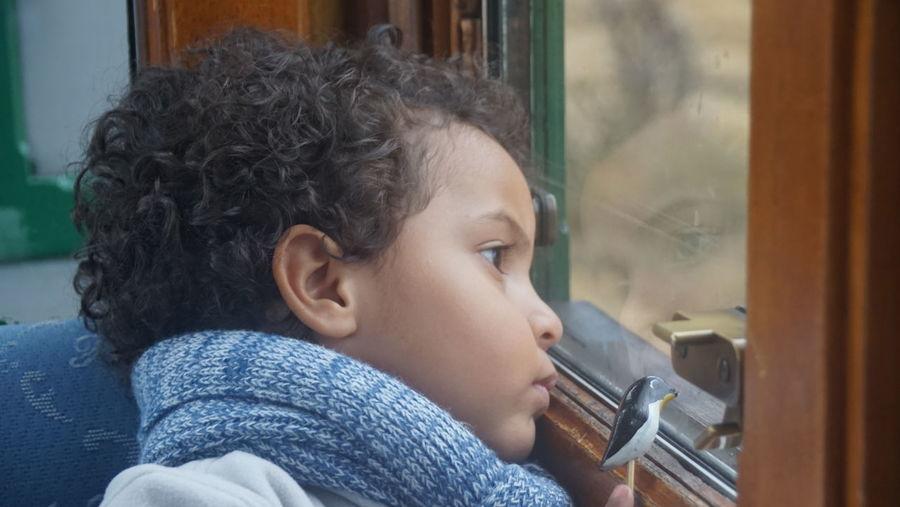 Close-Up Of Cute Boy Looking Through Train Window