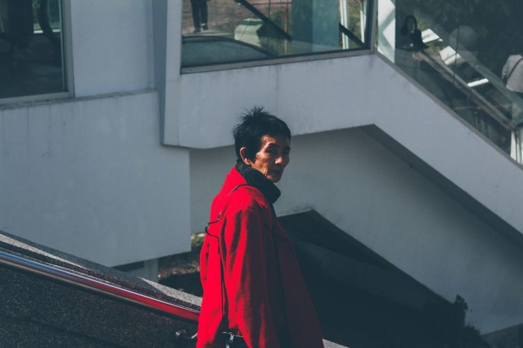 Side view of mature woman wearing red overcoat in city