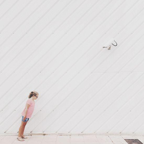 Girl standing on street against wall
