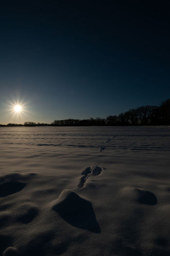 Scenic view of snowy landscape against clear sky at night