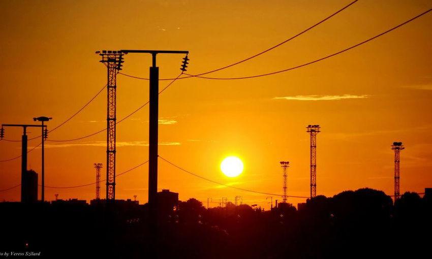 Silhouette electricity pylon on street against orange sky