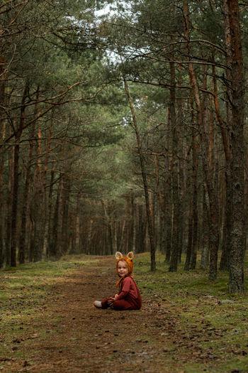 Toddler baby girl in bear bonnet sitting in the woods