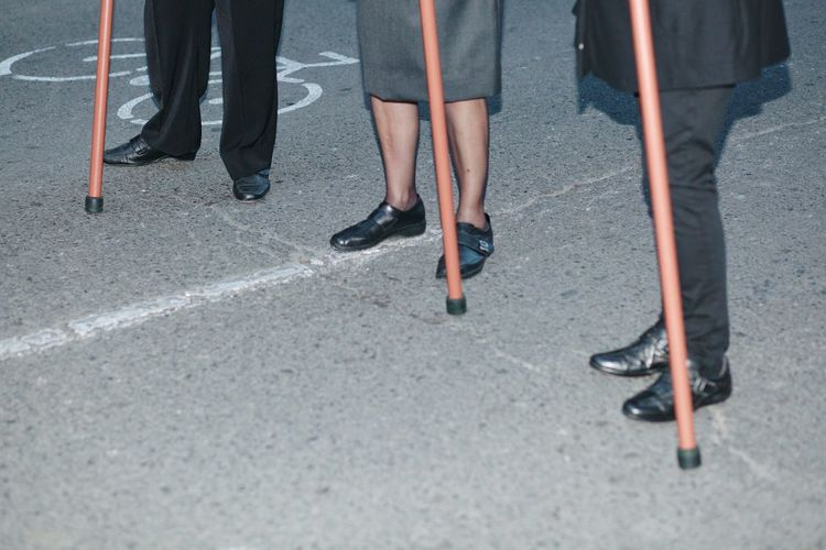 Low Section Of People With Walking Canes Standing On Street At Night