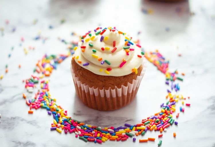 High Angle View Of Cupcake And Sprinkles On Table