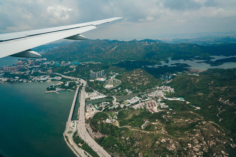 Aerial view of airplane flying over water against sky