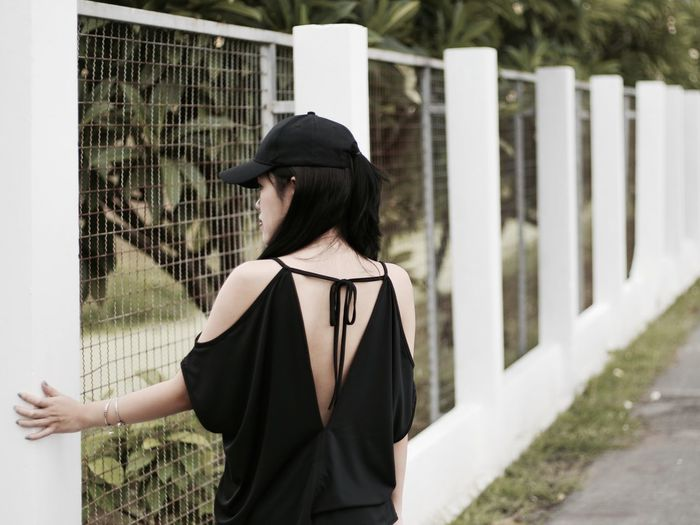 Rear view of woman standing against fence