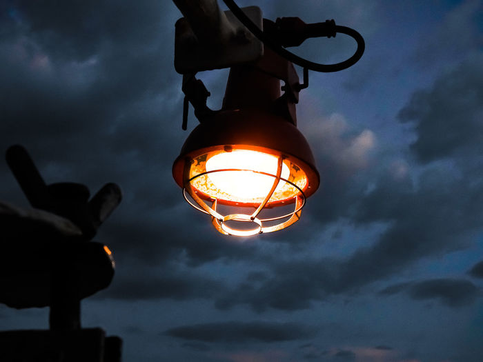 Low angle view of illuminated lamp against sky at sunset