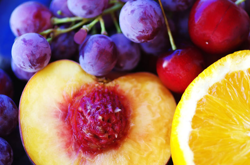 Close-Up Of Halved Peach And Grapes