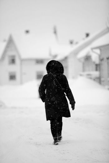 Rear View Of Woman Walking In Blizzard