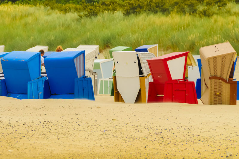 Multi colored chairs on sand at beach