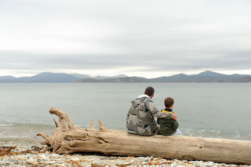 Father and son sitting on an old tree without bark on a sandy beach and admiring the blue clear sea