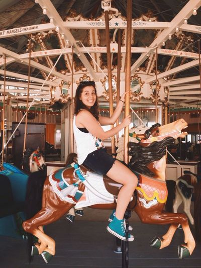 Side view portrait of happy woman riding merry-go-round