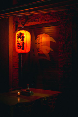 Sushi Restaurant Architecture Built Structure Candle Communication Dark Illuminated Indoors  Lantern Lighting Equipment Neon Night No People Orange Color Red Restaurant Sign Streetphotography Sushi Restaurant Text Wall - Building Feature Western Script